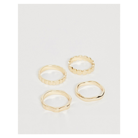 ASOS DESIGN pack of 4 rings in mixed texture designs in gold tone